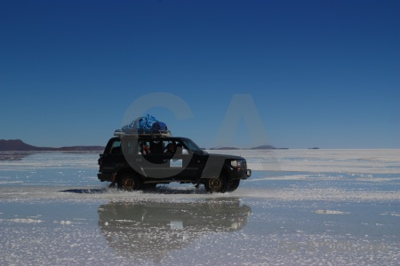 Bolivia salt flat sky vehicle water.
