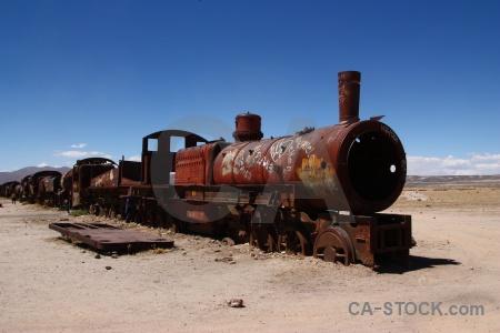 Bolivia vehicle train cemetery rust sky.