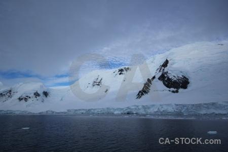Gunnel channel snow sea sky mountain.