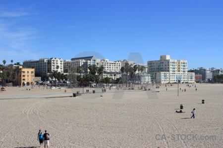 Person blue building cityscape beach.